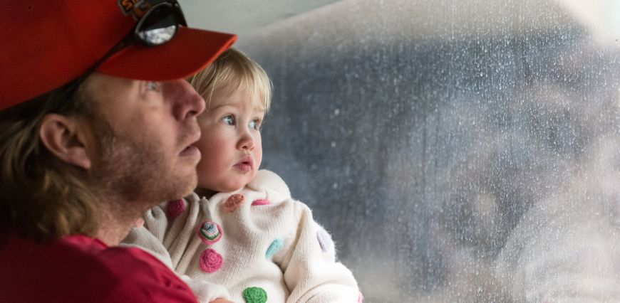 Little girl and father look through the window at the Pueblo Zoo penguin exhibit