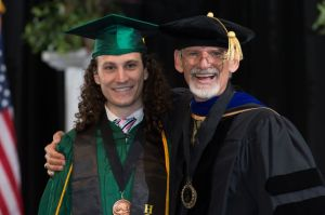 David Gilkey, Associate Professor of Environmental and Radiological Health Sciences, smiles and poses with graduating CSU student