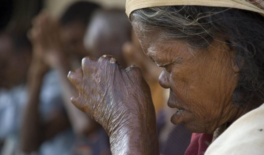 Woman affected by leprosy holds her hands near her face in a praying position.