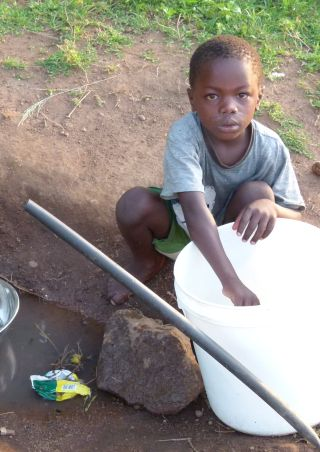 Tanzanian boy collecting water
