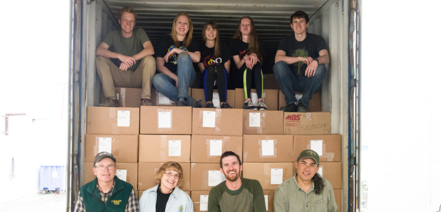Bob and Nancy Sturtevant (front row left), Ecology Ph.D. student Matt Luizza, and NREL research scientist Paul Evangelista take a break with volunteers from Alpha Phi Omega before they finish filling the shipping container with books for Hawassa University.