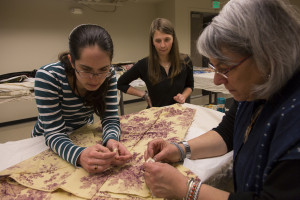 Graduate intern Rachel Crooks, left, works with volunteer Alana Eisemann and Dr. Susan Tontore on a French textile that dates back to 1820.