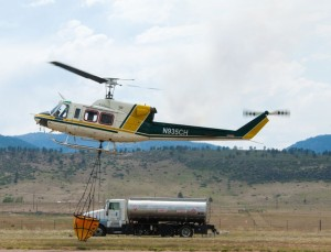 A helicopter takes off with a water bucket from the High Park Fire Incident Command Post at Colorado State University's Christman Field, June 15, 2012.