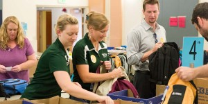 Colorado State University School Is Cool volunteers stuff backpacks with school supplies for Poudre School District students. August 6, 2014.