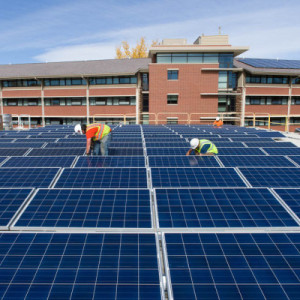 Contractors with Namaste Solar install an array of solar panels capable of powering 14 homes on the roof of Colorado State University's Braiden Hall, October 24, 2014.