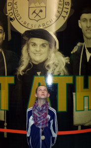 A future CSU student stands in front of a large mural in Moby Arena featuring Gill and several student-athletes.