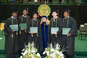 Dean Ann Gill congratulates student-athlete graduates at a College of Liberal Arts commencement ceremony.