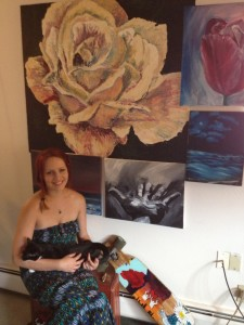 Dani Cole with her cat Neon spending time in her apartment where her art work is displayed.