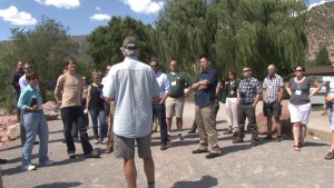 Jim Pokrandt, community relation director of the Colorado River District, talks with members of the Rams in the Rockies Tour along the banks of the Colorado River in Glenwood, Springs.