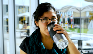 A student drinks from a reusable coffee mug