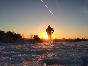 Silhouette of a runner on snowy winter morning
