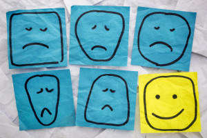 a set of sad, unhappy and happy, smiling faces - rough sketches on isolated blue and yellow sticky notes