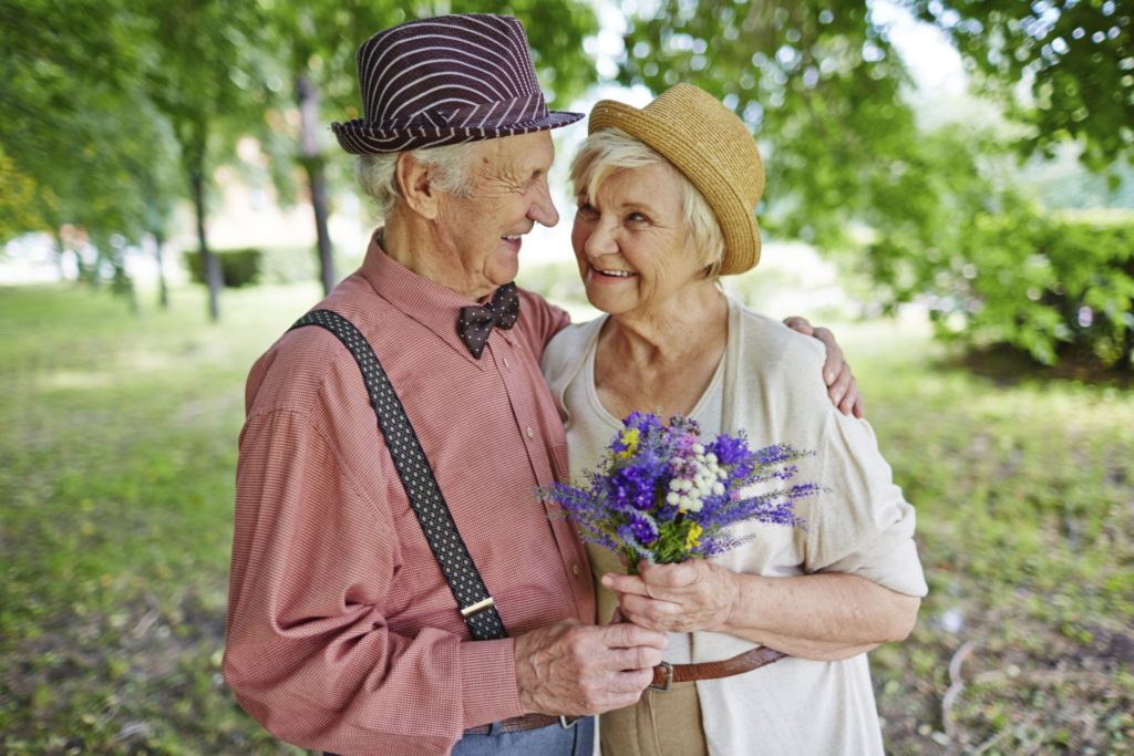 Mature couple with flowers outdoors