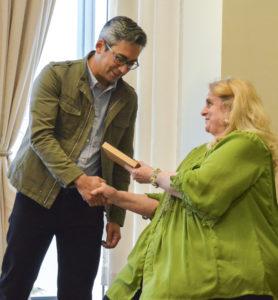 Eric Ishiwata accepts his award from Dean Ann Gill.