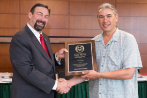 Colorado State University President Tony Frank presents Natural Resource Ecology Laboratory research scientist Paul Evangelista with the Ram Pride Service Award for his work supplying textbooks to Ethiopia's Hawassa University.