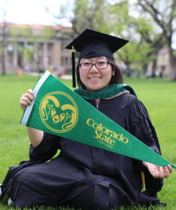 Girl with Colorado State pennant sitting on Oval.