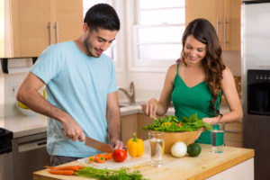 Attractive man and woman prepping low calorie dinner in kitchen very health conscious