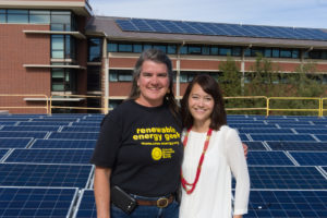 Colorado State University Facilities Engineer Carol Dollard and Housing and Dining Services Director of Communications Tonie Miyamoto pose as a solar array is installed on the roof of Braiden Hall, October 24, 2014.