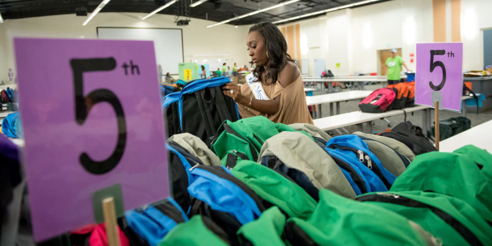 Miss Colorado 2016 Shannon Patilla and her volunteer partner Jeff Dodge help organize and stuff backpacks at the 25th Anniversary of School is Cool. August 10, 2016