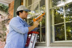 Man on ladder caulking outside window