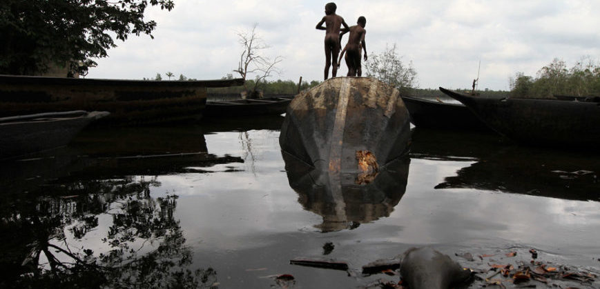 Boys on top of a tipped oil tank in a polluted lake.