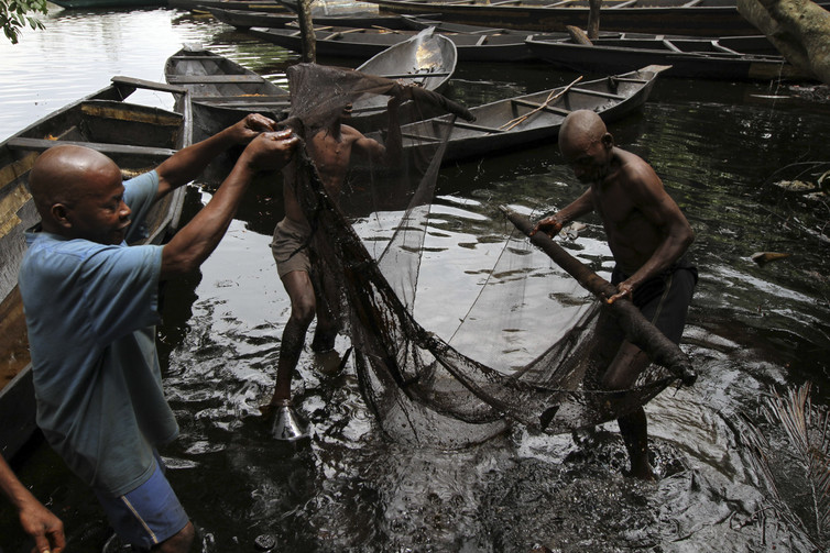Fishermen hauling net through polluted water by boats.