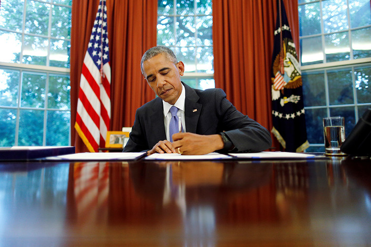 President Barack Obama signing papers at his desk in the Oval Office.