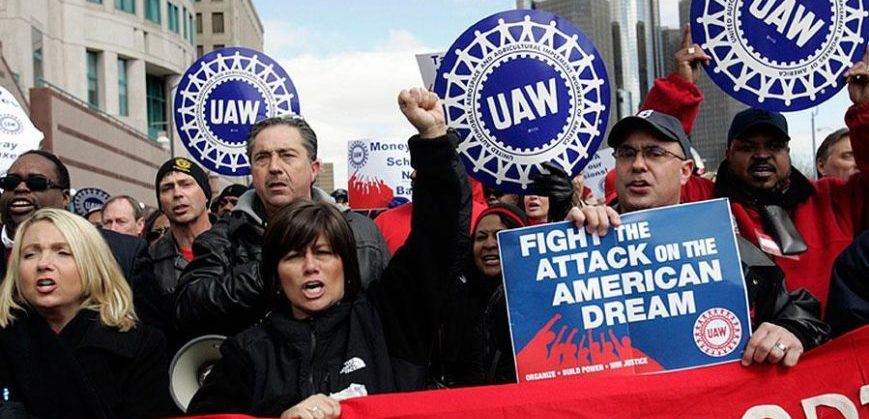 UAW members hold signs saying Fight the Attack on the American Dream