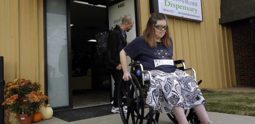 Woman in wheelchair outside building with a Dispensary sign