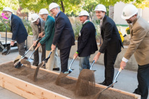 seven people with shovels and hardhats turning over soil in a groundbreaking ceremony