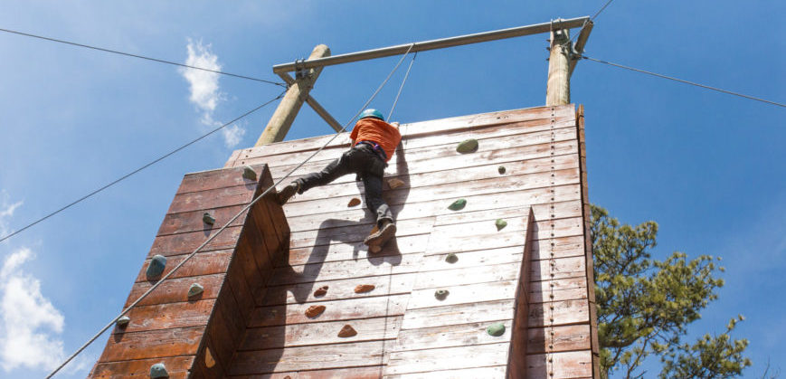 LONE CLIMBER ON OUTDOOR CLIMBING WALL