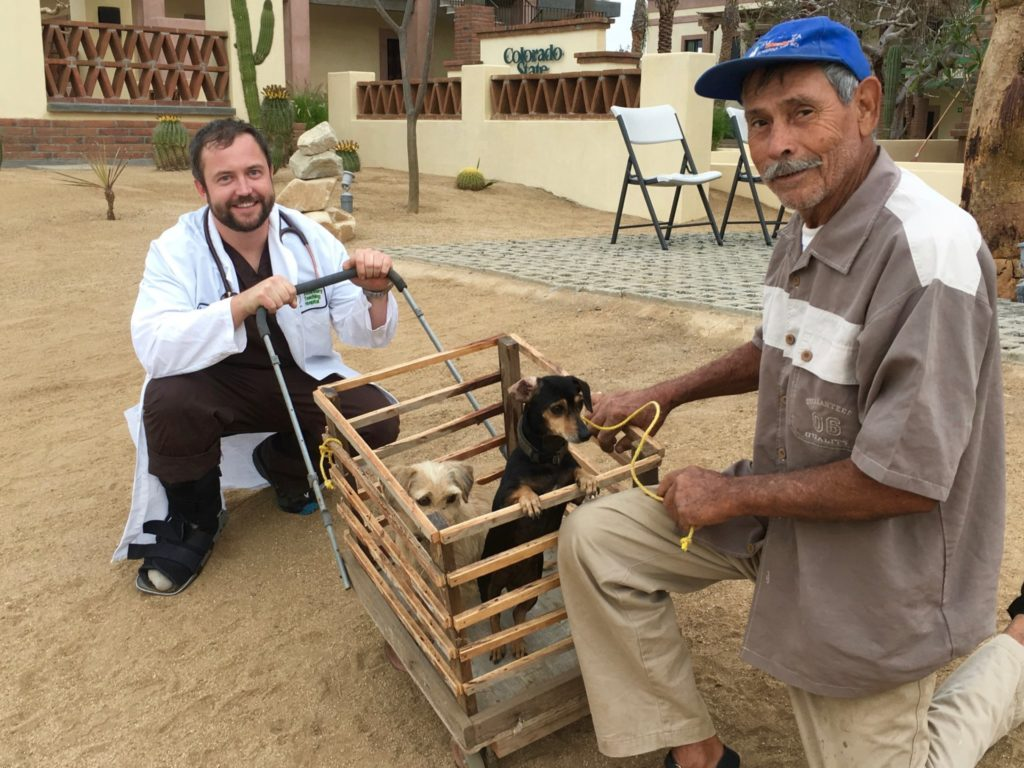 """Dr. Cody Minor assists a man with his dogs at the CSU Todos Santos Center in Baja California Sur. """"Cody helped to change the way people think about their animals,"""" said Amy Rex, a Todos Santos native who works at the center."""