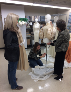 Volunteers Jan Alexander (left) and Mary Biggers (right) assist acting curator/collections manager Megan Osborne in dressing a mannequin with the 1890 wedding gown, following Mary's careful work to reattach the original leg-of-mutton sleeves to the bodice.