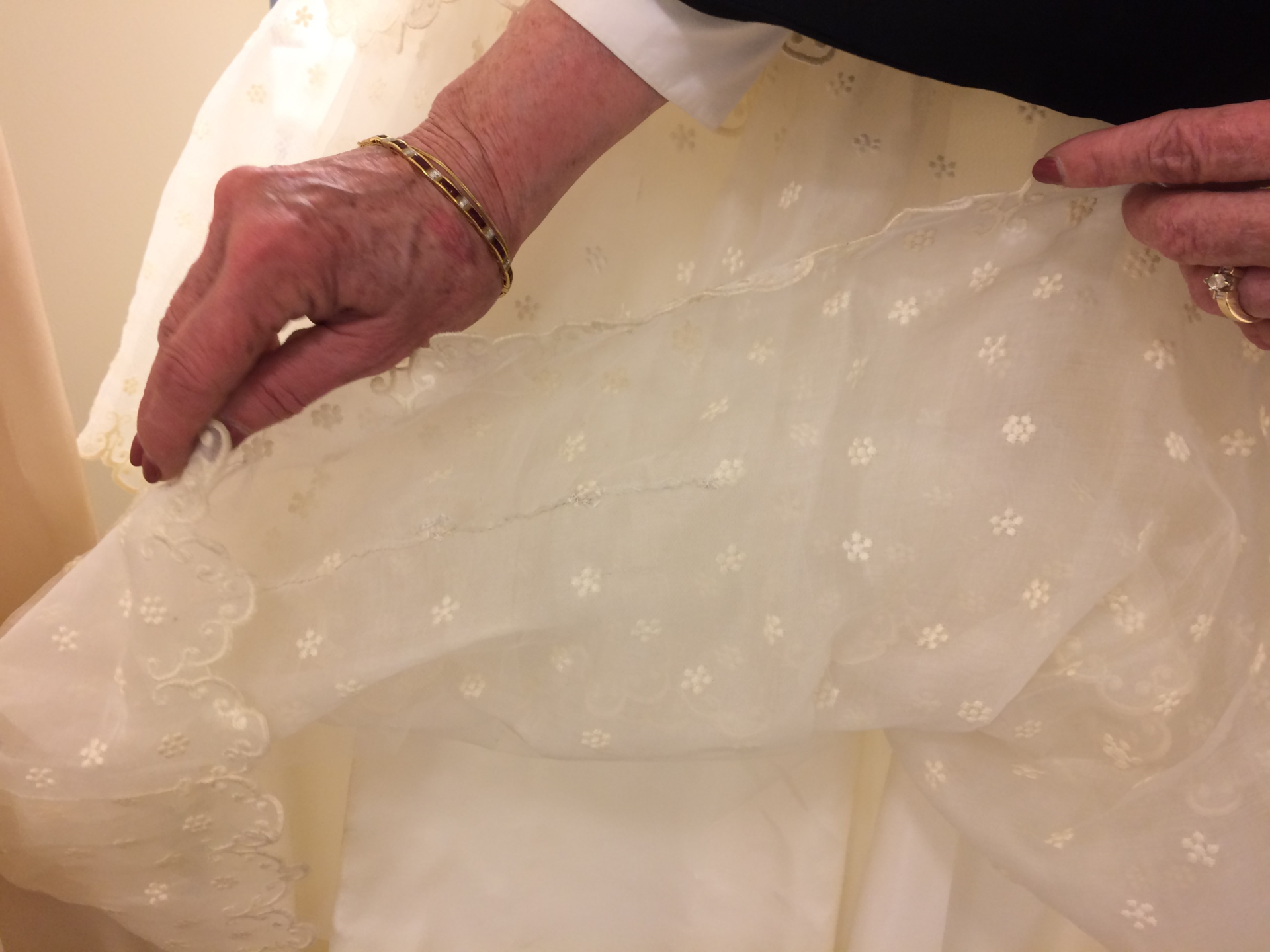 Close up of Mary Biggers fixing the 1950s organza wedding dress