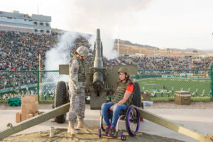 Amy Van Dyken in wheelchair with cadet firing cannon.