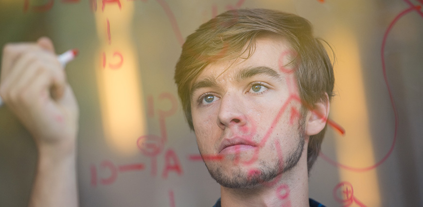 Portrait of microbiology student Joshua Daum, taken as he writes equations on a glass board