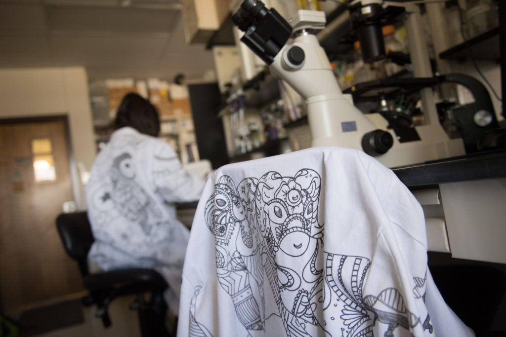 Lani Benedict, a sophomore in microbiology, embellishes lab coats to reflect scientific inspiration and research focus. (John Eisele/CSU Photography)