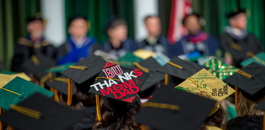 "Graduation caps at College of Veterinary Medicine and Biomedical Sciences. One reads ""BU Thank$ Mom & Dad"""