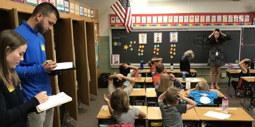 College students take notes as children follow their instructor in putting their hands on their head in a classroom
