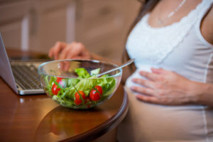 Pregnant woman with salad