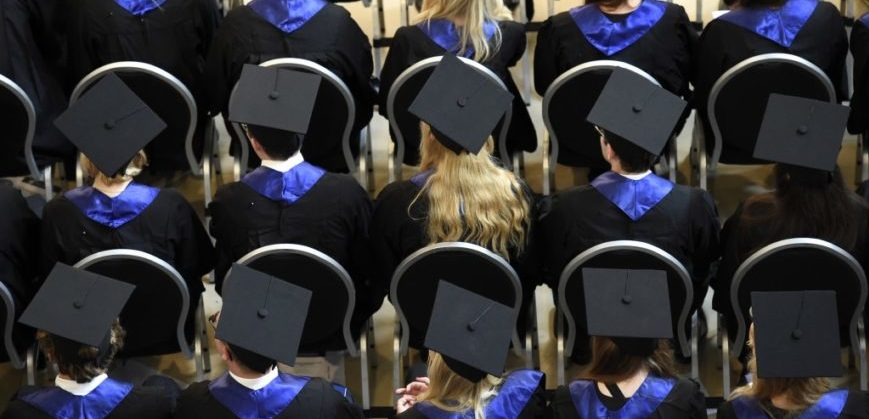 STUDENTS IN CAPS AND GOWNS SEATED