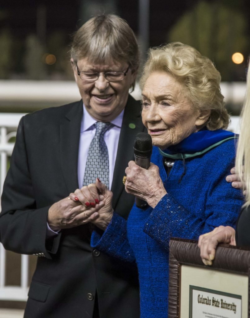 Dr. Wayne McIlwraith holding hands with Princess Abigail Kawananakoa as she speaks into a microphone.