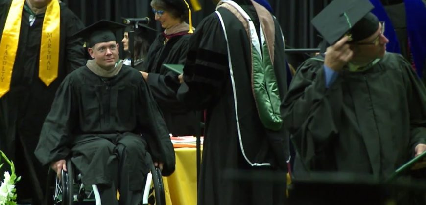 Kevin Hoyt wheels offstage in his cap and gown after getting his diploma in his wheelchair