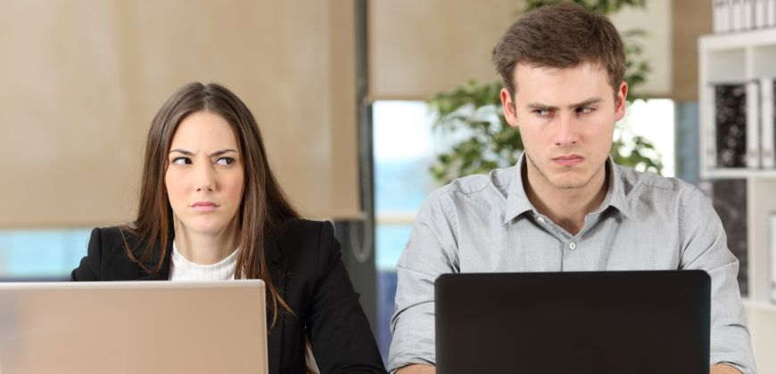 Woman and man on laptops giving each other angry side-glances