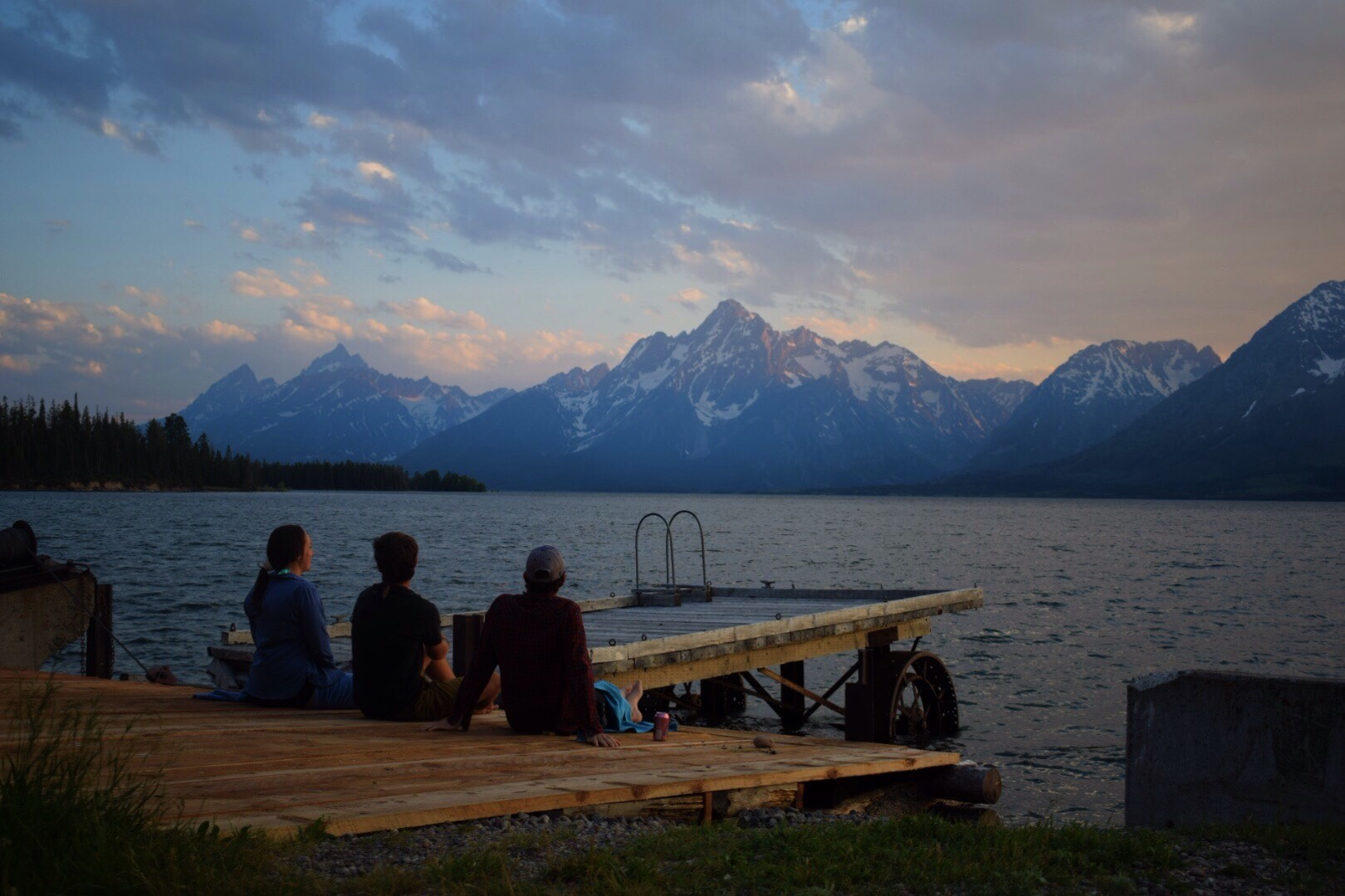 three people sitting on dock near lake in Grand Teton National Park