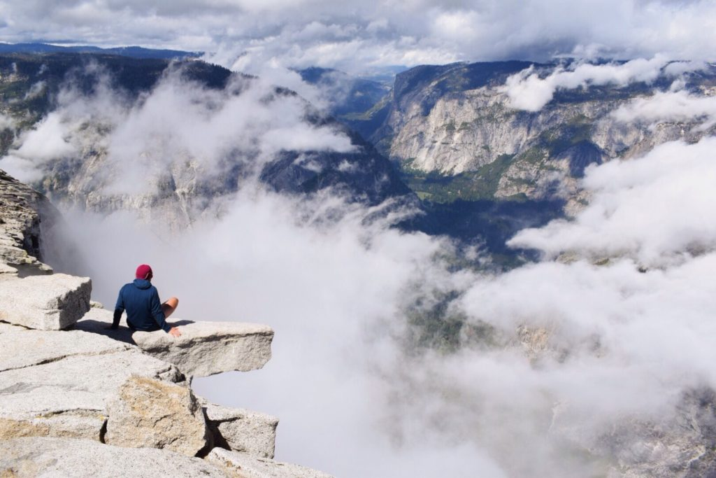 person sitting on cliff at Yosemite National Park
