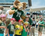 CSU mascot posing with a group of children in front of stadium