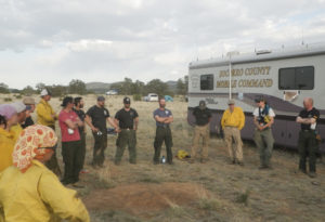 group of individuals standing in a circle outside a mobile command center