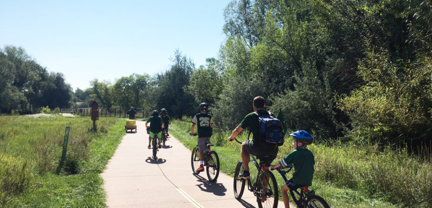 Color photo of a family biking to first CSU football game on the Spring Creek Trail