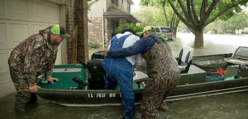 Two men help elderly man into boat in flooded driveway